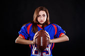 istock athletic brunette posing as american football girl on black background 1261720666