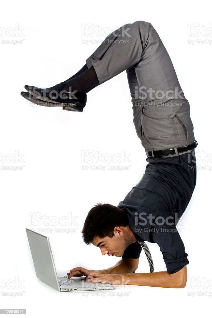 Athletic businessman using laptop in awkward position stock photo