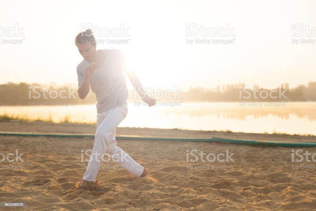 Intérprete de capoeira Atlético fazendo movimentos na praia - Foto de stock de Adulto royalty-free