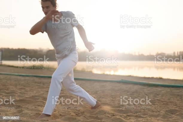 Foto de Intérprete De Capoeira Atlético Fazendo Movimentos Na Praia e mais fotos de stock de Adulto
