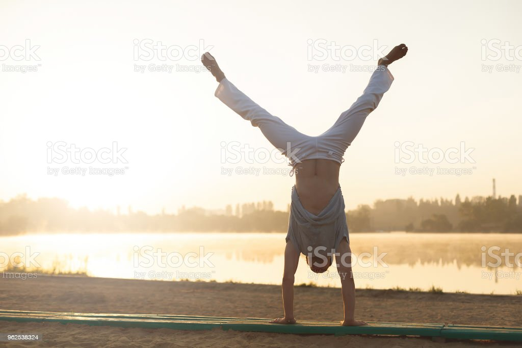 Athletic capoeira performer workout training on the beach sunris - Royalty-free Adult Stock Photo