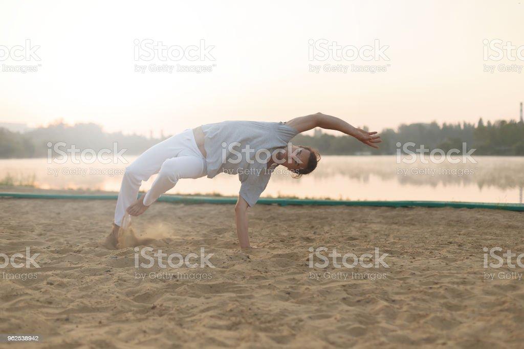 Formação de treino de executante de capoeira Atlético sobre a praia sunris - Foto de stock de Adulto royalty-free