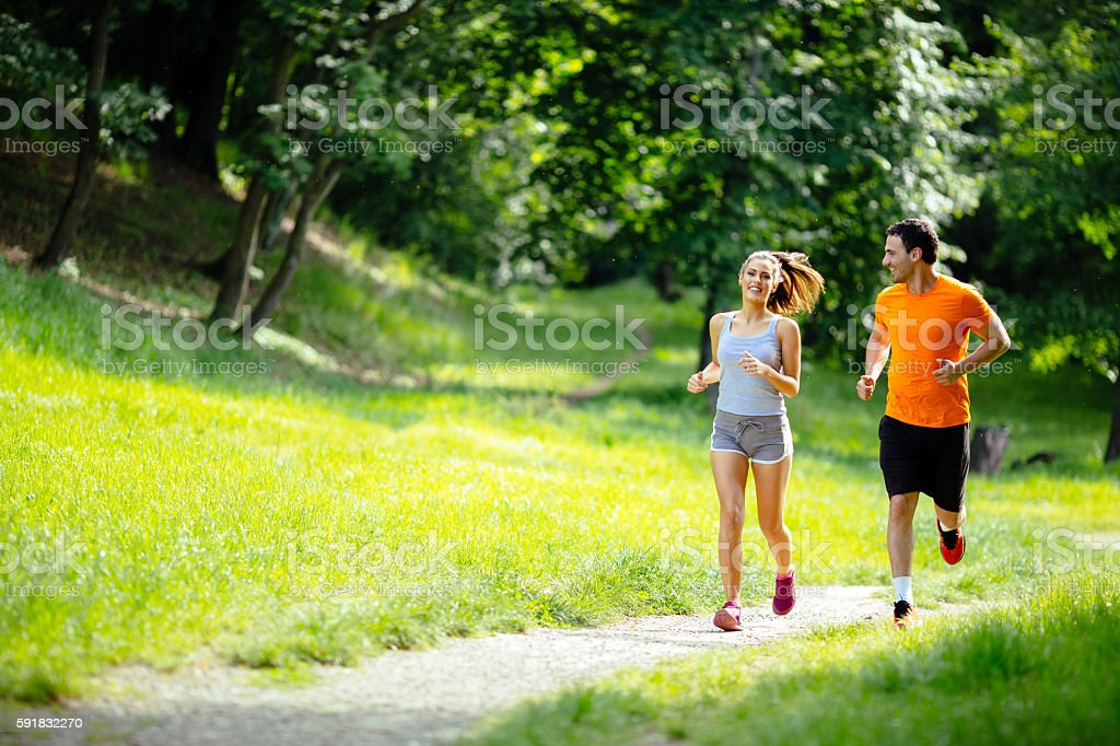 Athletic couple jogging in nature – Foto
