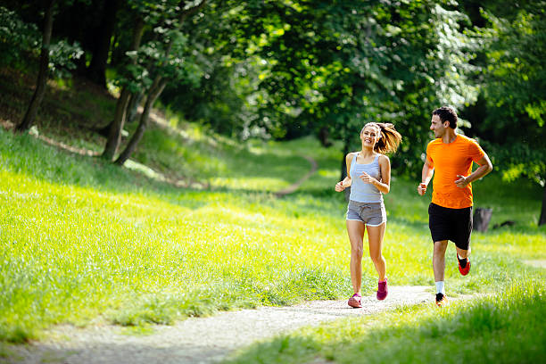 Athletic couple jogging in nature - Photo