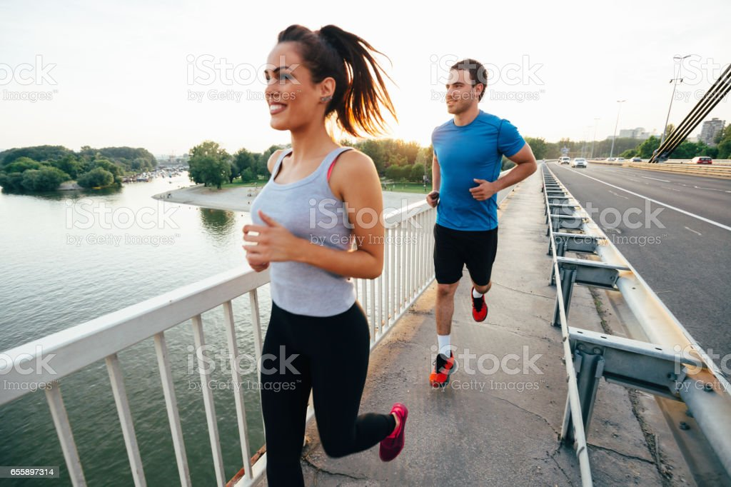 Athletic couple jogging together outdoors stock photo