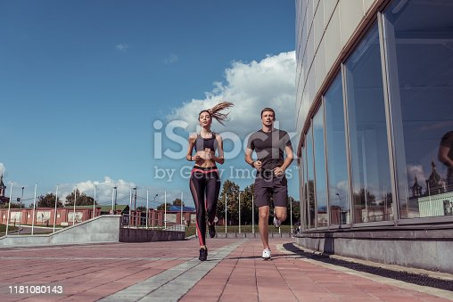 Athletic couple man woman, summer in city, jogging in jump, free space for text motivation fitness and workout, sportswear. Background tile glass windows.