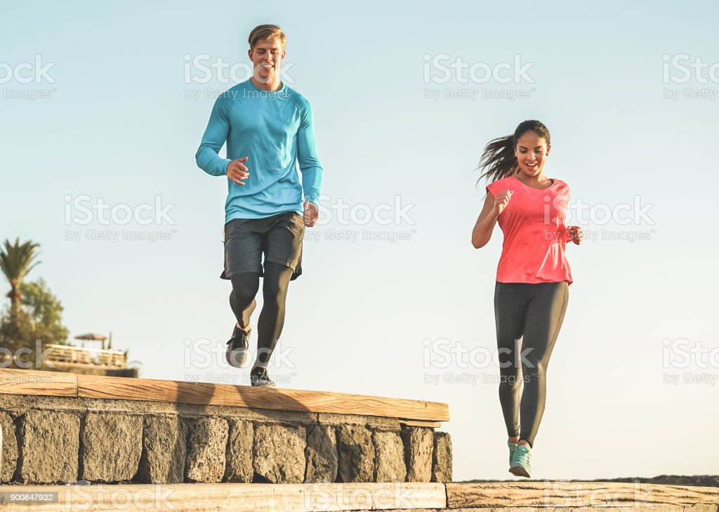 Athletic Couple Of Friends Running Outdoor In City Park