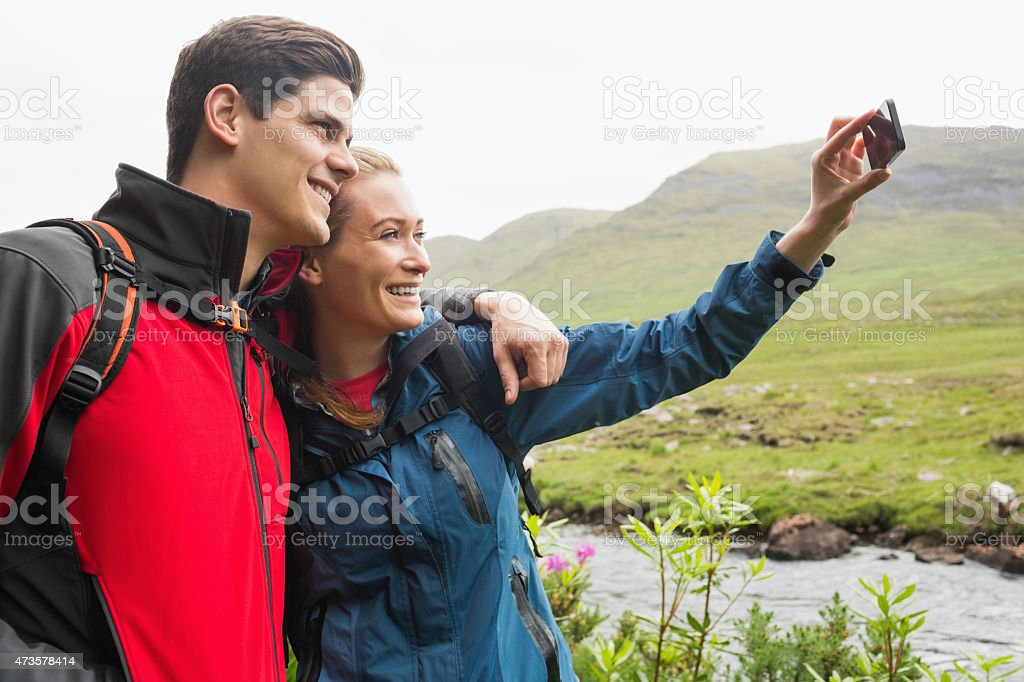 Athletic couple on hike taking a selfie stock photo