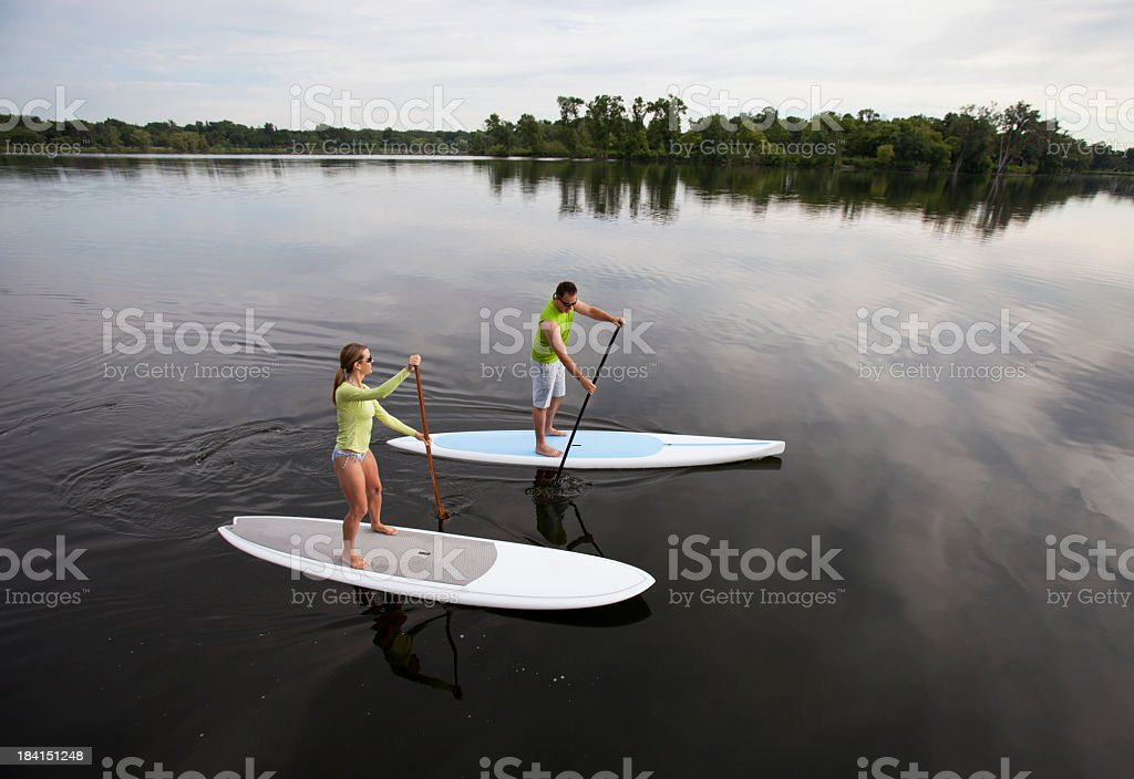 Athletic Couple Paddle Boarding on a Calm Midwestern Lake. royalty-free stock photo