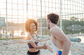 Young man shaking hands with woman on the beach after they finished a game of volleyball