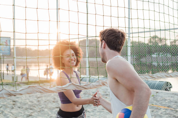 Athletic couple shaking hands after beach volleyball stock photo