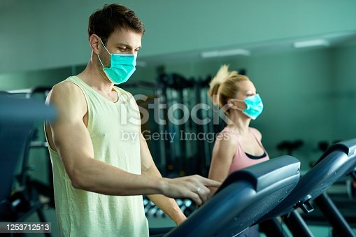 Athletic couple running on treadmill while wearing protective face masks at health club. Focus is on man.