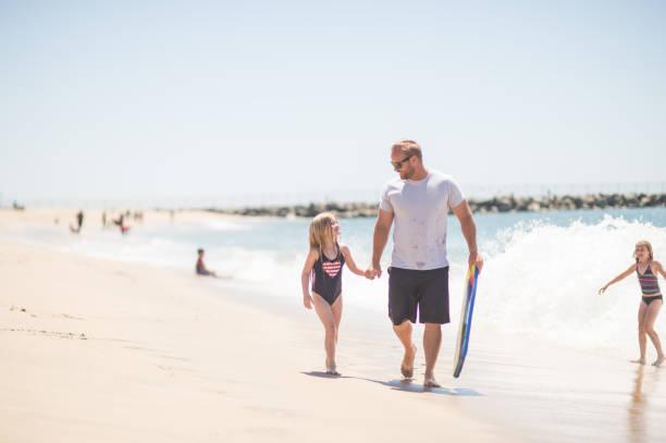 athletische papa spielt mit seinem mädchen am strand an einem sonnigen nachmittag - kitesurfen lernen stock-fotos und bilder