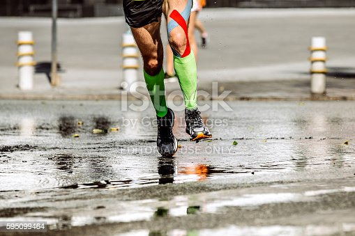 Ekaterinburg, Russia - August 7, 2016: athletic feet men runner's compression socks and knee taping during Marathon Europe-Asia