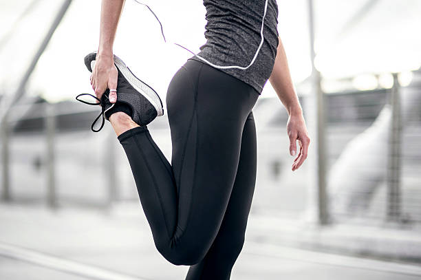 Athletic female figure stretching wearing running pants stock photo