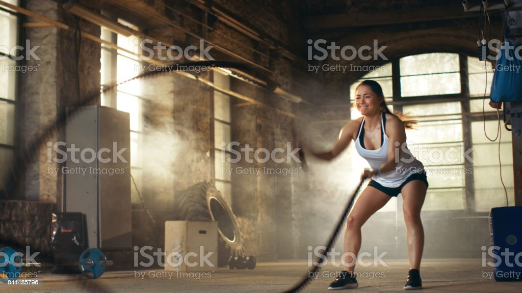 Athletic Female in a Gym Exercises with Battle Ropes During Her Cross Fitness Workout/ High-Intensity Interval Training. She's Muscular and Sweaty, Gym is in Deserted Factory. stock photo