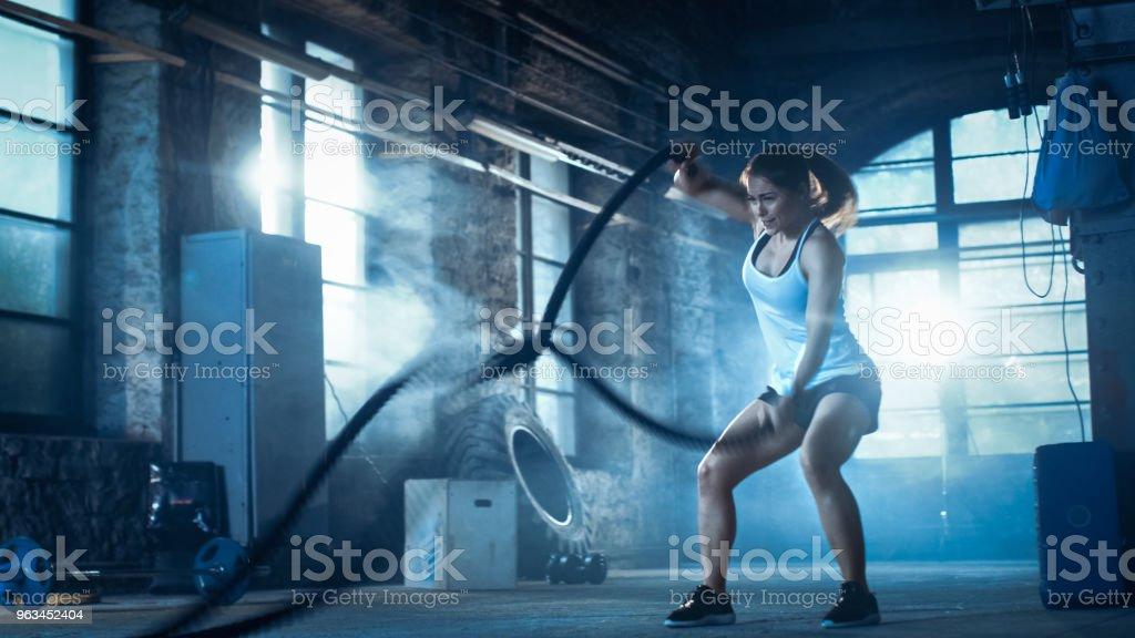 Bir spor salonunda atletik erkek egzersizleri ile savaş ipler onun egzersiz sırasında / yoğun aralığı eğitim. Kas ve ateşli bir kız, spor salonu terk fabrikada. Soğuk ortam. - Royalty-free Aktif Hayat Tarzı Stok görsel