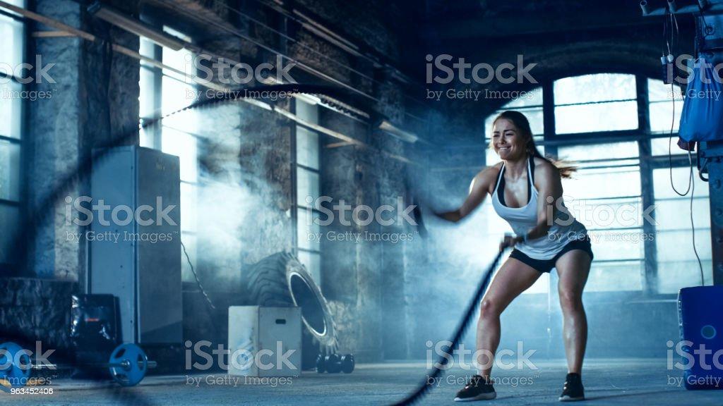 Athlétique féminin dans un gymnase exerce avec des cordes de bataille au cours de son entraînement / haute intensité Interval Training. Elle est musculaire et Sweaty, Gym dans l'usine déserte. Froid ambiant. - Photo de A l'abandon libre de droits