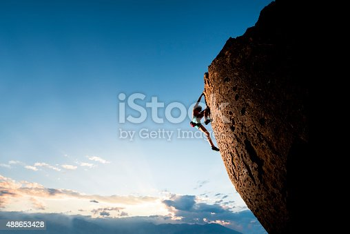 Strong female rock climber on a steep overhanging cliff at sunset