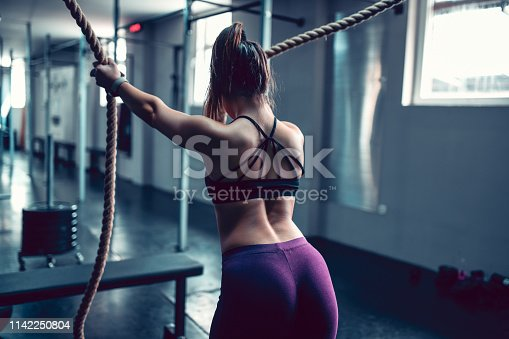 Athletic Female Working Out With Ropes In Gym