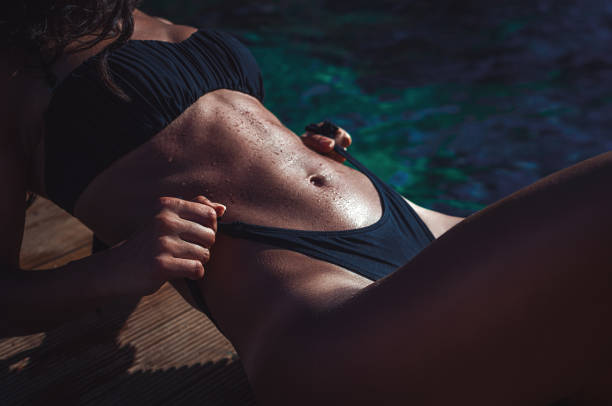 Athletic fit body woman in swimsuit sunbathing by the sea showing her perfectly shaped body and abs stock photo