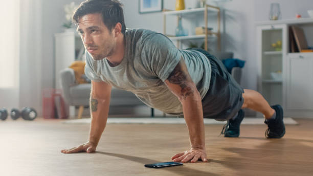 Athletic Fit Man in T-shirt and Shorts is Doing Push Up Exercises While Using a Stopwatch on His Phone. He is Training at Home in His Living Room with Minimalistic Interior. Athletic Fit Man in T-shirt and Shorts is Doing Push Up Exercises While Using a Stopwatch on His Phone. He is Training at Home in His Living Room with Minimalistic Interior. only young men stock pictures, royalty-free photos & images