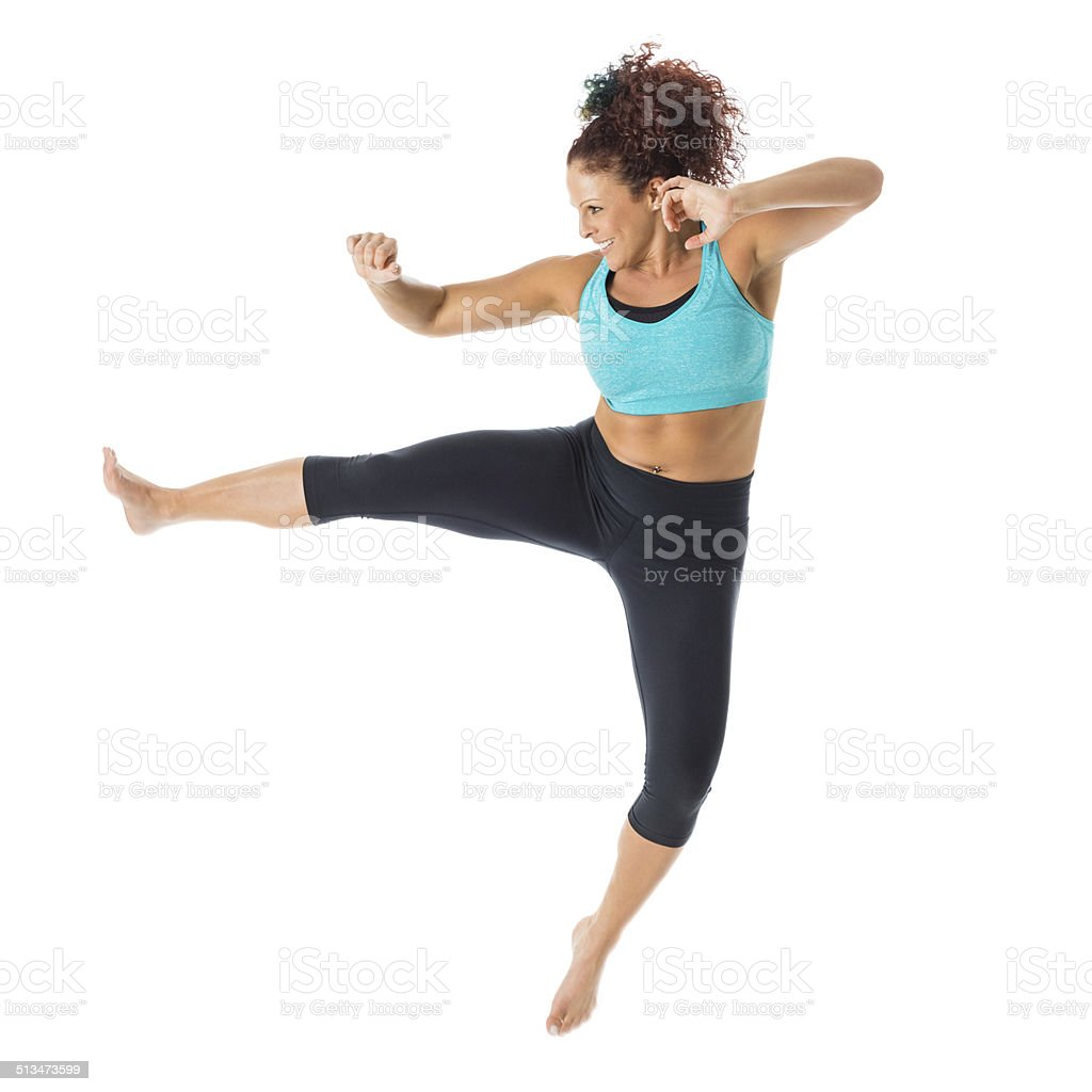 Athletic fitness instructor performing kickboxing exercise routine; studio shot stock photo