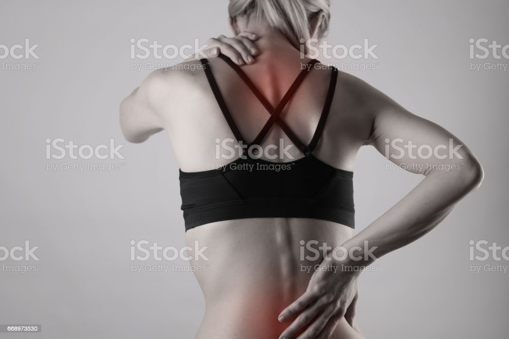 Athletic fitness woman suffering from back pain . Sports exercising injury. stock photo