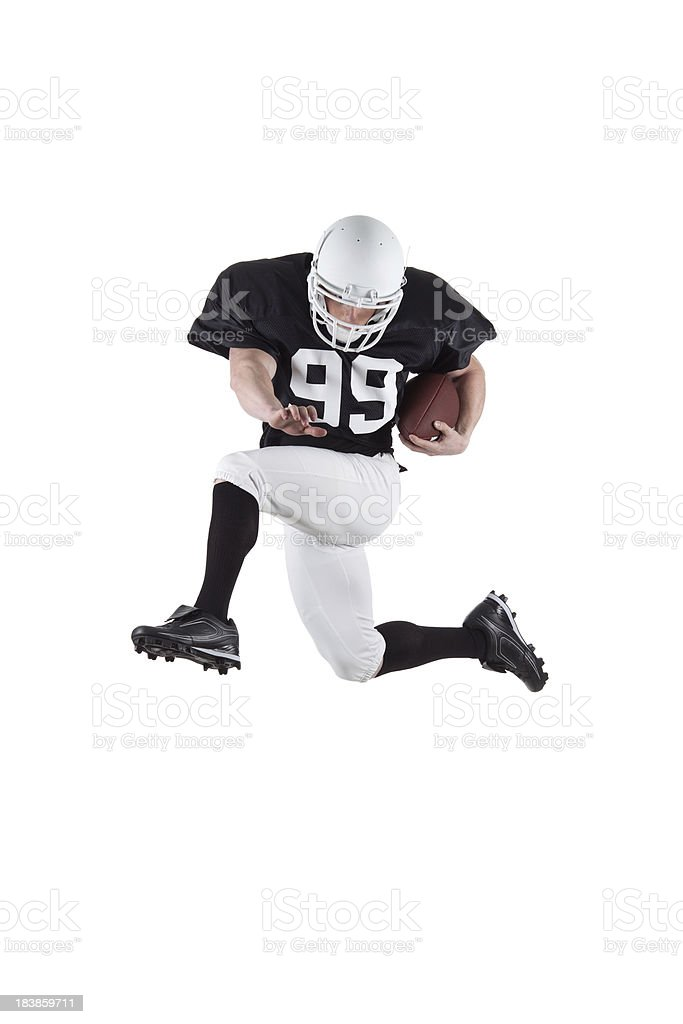 Athletic football player jumping through the air stock photo