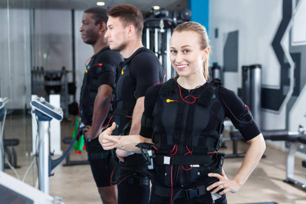 Athletic  girl during electric muscle stimulation workout in fitness gym Athletic  smiling cheerful  girl during electric muscle stimulation workout in fitness gym electro music stock pictures, royalty-free photos & images