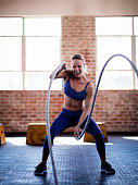 Young adult caucasian girl doing battle ropes exercise on a gym workout at the gym