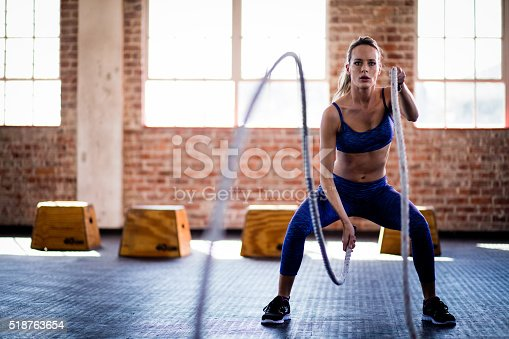 istock Athletic girl focused on fitness training with ropes at gym 518763654