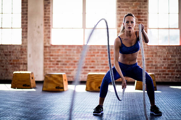 Athletic girl focused on fitness training with ropes at gym stock photo