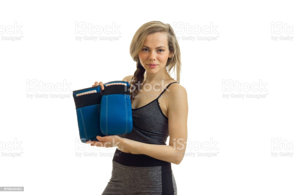 7b47df8d86a8 Athletic girl looks into the camera and holds boxing gloves is isolated on  a white background - Stock image .