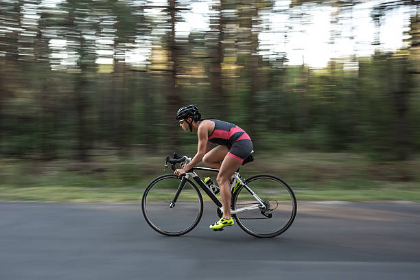 Athletic girl rides a bike stock photo