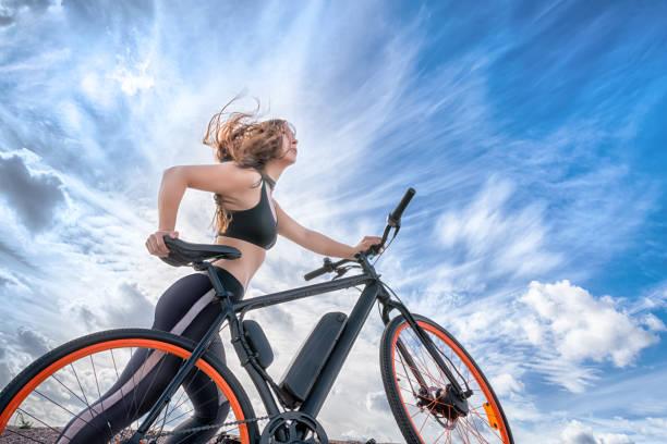 sportliche mädchen mit haaren im wind führenden e-bike. - elektrorad stock-fotos und bilder