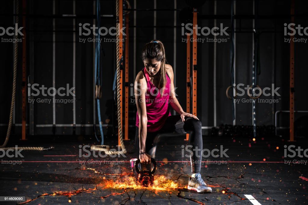 Athletic girl works out at the gym with a fiery kettlebell foto stock royalty-free