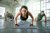 Female leads gym power yoga group class strength determination drive as physical trainer instructor in push ups intense focused expression. Fitness exercise gym group muscle building workout with woman leading group of people