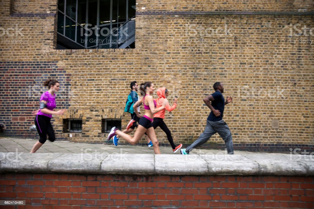 Athletic group of urban runner people exercising in London royalty-free stock photo