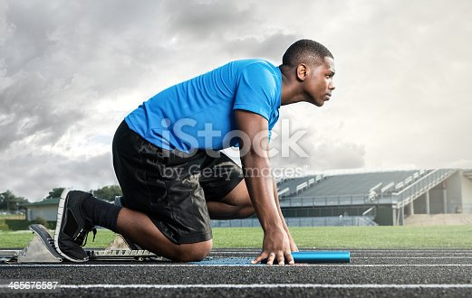 istock Athletic High School Track Star on Starting Block Before Race 465676587