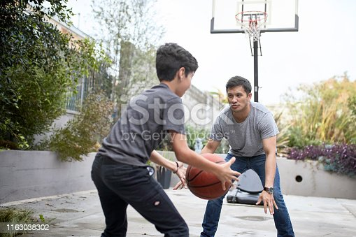 Hispanic father playing basketball outdoors with his young son and teaching him how to fake out an opponent.