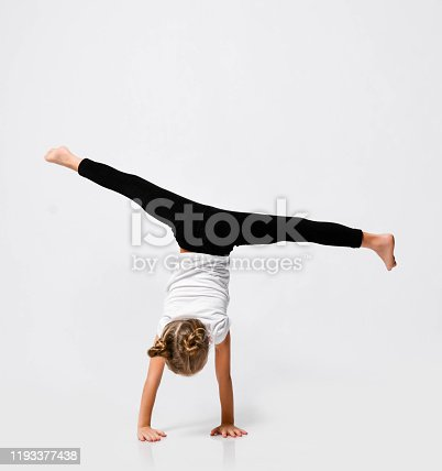 Slim athletic blonde kid girl is doing gymnastic acrobatics exercises, handstand and stretching with her legs up on white with free copy space