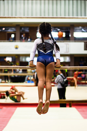 istock Athletic little girl gymnast performing exercises at the bar 1059819458
