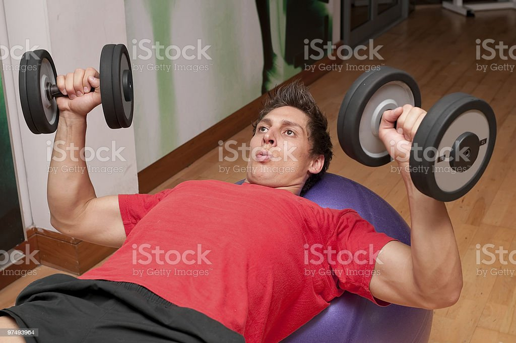 Athletic male doing dumbbell press on a fitness ball royalty-free stock photo