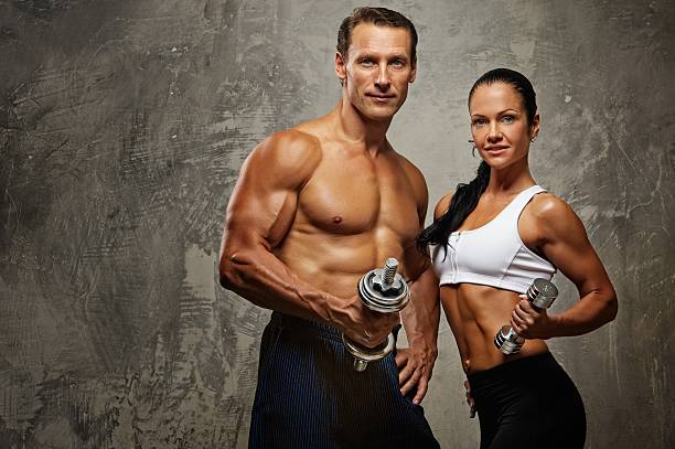 Athletic man and woman with a dumbbells. stock photo