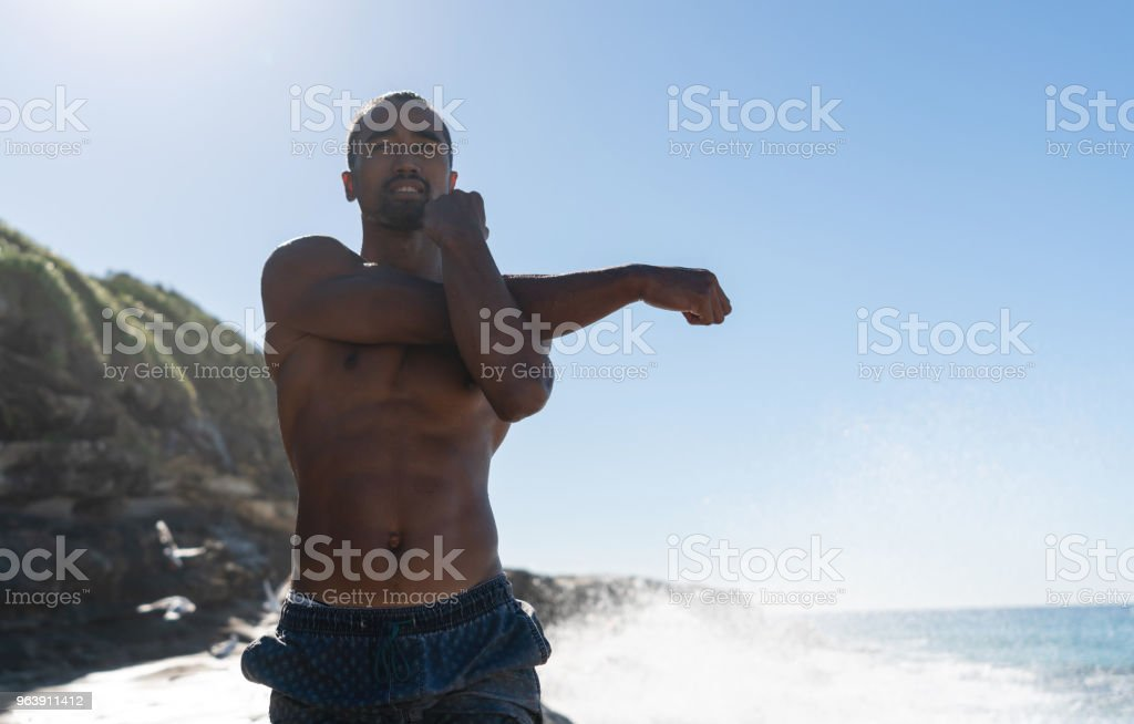 Athletic man at the beach stretching his arms - Royalty-free Adult Stock Photo