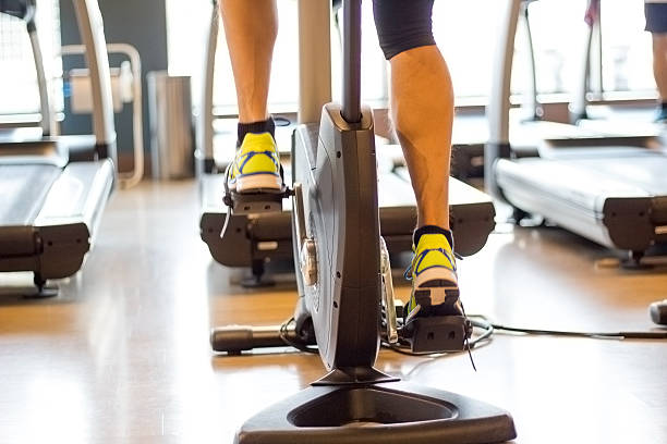 Athletic man cycling on stationary bike in gym Athletic man cycling on stationary bike in gym. Focus on leg. exercise bike stock pictures, royalty-free photos & images