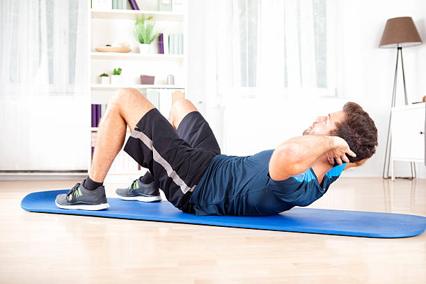 athletic man doing curl ups exercise at home - sit ups stock photos and pictures