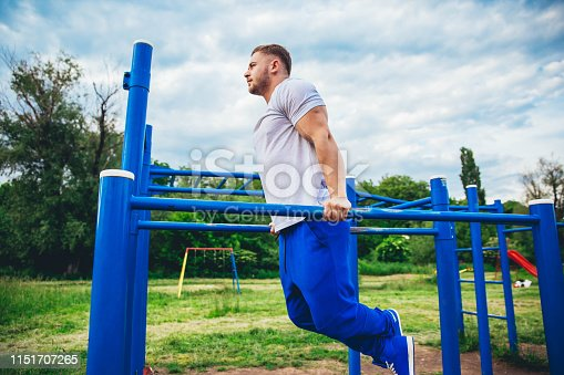 Athletic man doing push ups on parallel bars