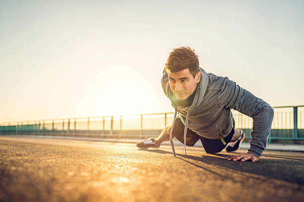 athletic man doing push-up on a road at sunset. - push up stock photos and pictures